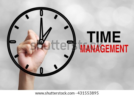 Hand is drawing a clock with text Time Management Concept aside with blurred gray background. - stock photo