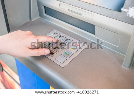 Hand is entering pin code in ATM machine to withdraw cash. Banking concept.