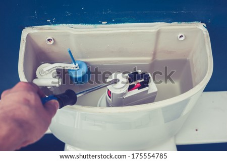 Hand is fixing a toilet cistern at home