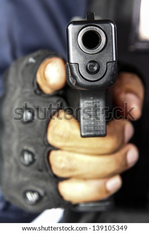 Hand is holding a gun - stock photo
