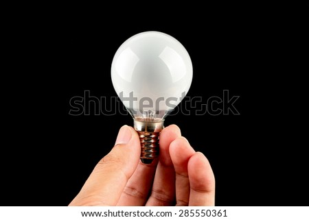 Hand is holding a light bulb with black background. - stock photo