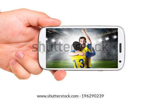 hand is holding a modern phone with soccer or football player on screen - stock photo