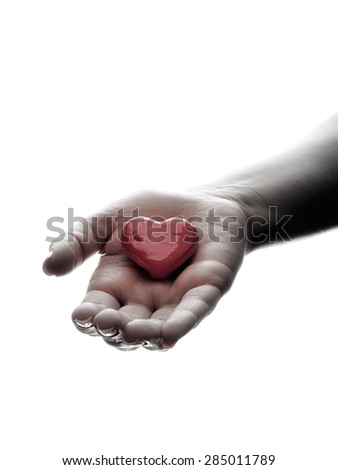 Hand is holding a red heart on a white background. - stock photo