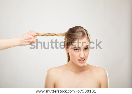 hand is holding blond woman's hair - stock photo