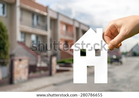 Hand is holding cut out paper house as symbol for real estate - stock photo