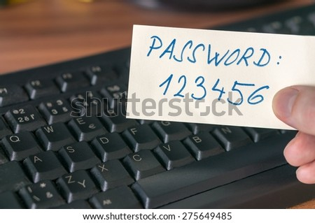 Hand is holding paper with password near keyboard - stock photo