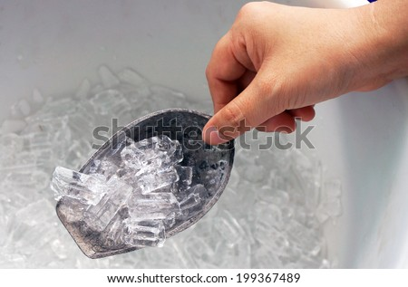 Hand is holding the ice scoop, in a cooler packed with ice.                               - stock photo
