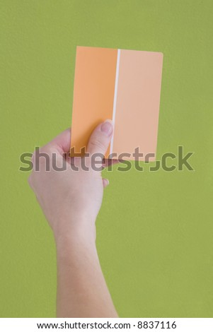 Hand is holding up an orange paint sample to a green wall.