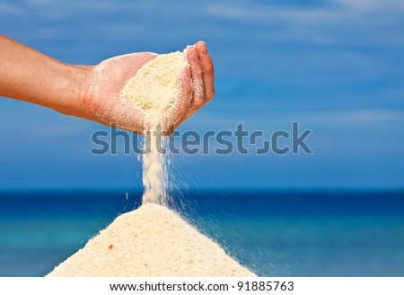 Hand is pouring coral sand on a beach - stock photo