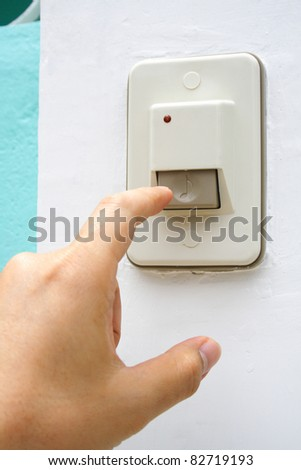Hand is pushing an entrance electronic doorbell
