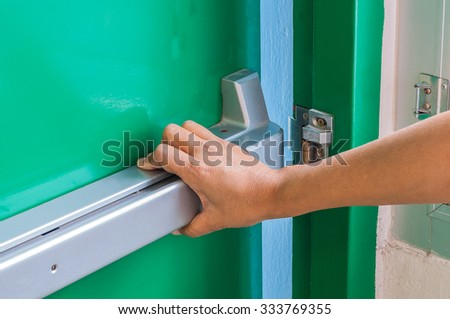 Hand is pushing/opening the emergency fire exit door - stock photo