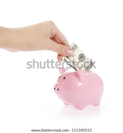 hand is putting money into piggy bank on white background - stock photo