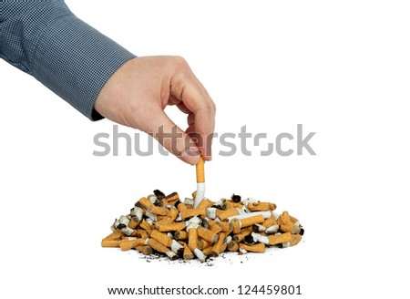 hand is putting out a cigarette on many cigarette butts - stock photo