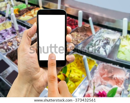 hand is searching the best ice cream shop with the smartphone and the ice creams on the background  - stock photo