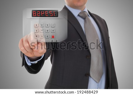 Hand is setting code of security alarm system - stock photo