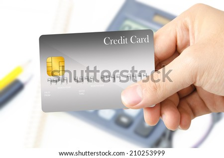 Hand is showing the gray blank template credit card on the office stationary blur background. - stock photo