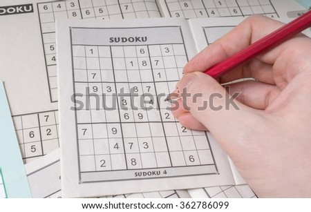 Hand is solving sudoku crossword, popular puzzle game. - stock photo