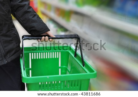 hand is taking the shopping basket in the market - stock photo