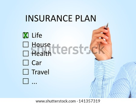Hand is writing insurance plan. - stock photo