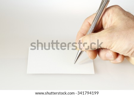 hand is writing on a white paper note
