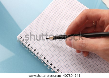 hand is writing on blank notebook - stock photo