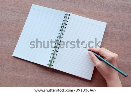 hand is writing on blank notebook with pencil on wood textures  - stock photo