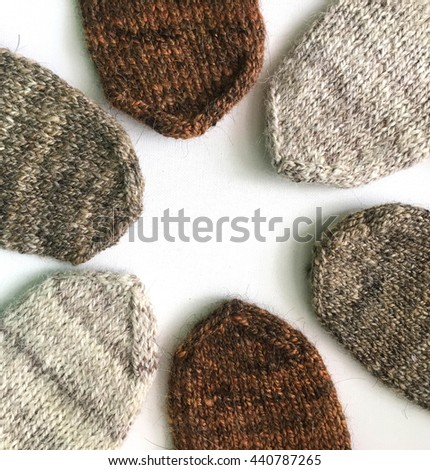 Hand knit mittens laying in a circle on a white surface. - stock photo