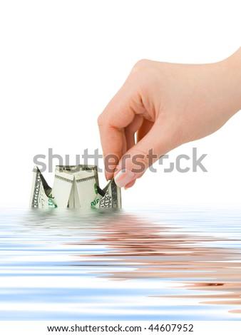 Hand launching money ship isolated on white background - stock photo