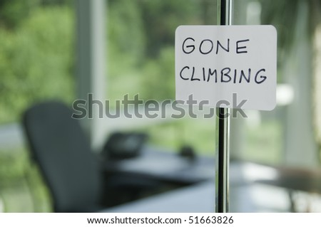 Hand-lettered sign on glass door to office: GONE CLIMBING (shallow field of depth) - stock photo