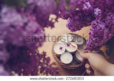 Hand lighting small white candles in a basket and lilac - stock photo