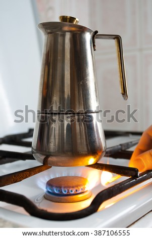 hand lighting the gas under the coffeepot - stock photo