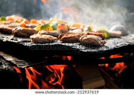 hand-made bbq in forest with beacon and vegetable on stone plate  - stock photo
