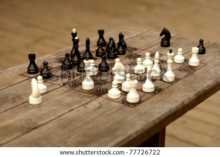 hand-made chessboard on wooden table, selective focus - stock photo