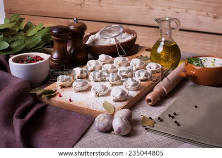 hand-made dumplings on the board with flour and ingredients - stock photo