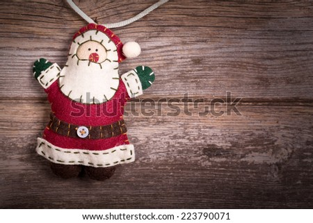 Hand made felt Santa Claus Christmas decoration. Vintage style, over old wood background, with space for your text. - stock photo