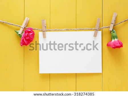 Hand made greeting card with carnations on yellow wood background - stock photo