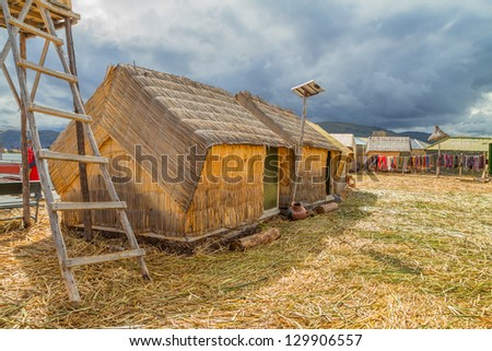 Hand made houses in Uros with solar panels, artificial islands made of floating reeds, Peru, South America.