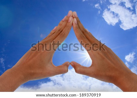 Hand made �¢??�¢??in a heart shape with the sky and the sun - stock photo