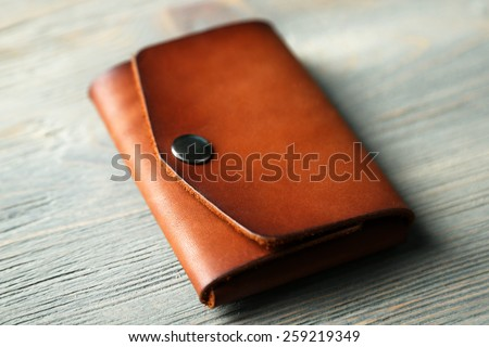 Hand made leather man wallet on wooden background - stock photo