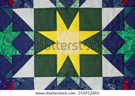 hand made quilt detail with colorful patterned cloth - stock photo