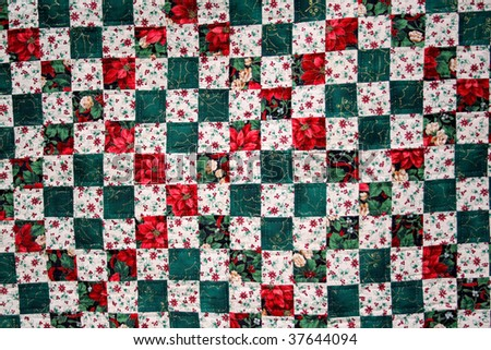 Hand made quilt.  Hand stitching for a rustic, home made look. Christmas patchwork with a floral print. - stock photo