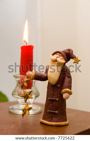 Hand made Santa and a candle. - stock photo