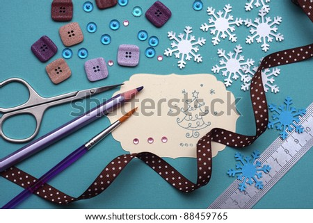 hand made scrapbooking post card and tools lying on a table - stock photo