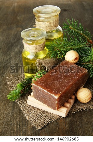Hand-made soap and bottles of fir tree oil on wooden background - stock photo