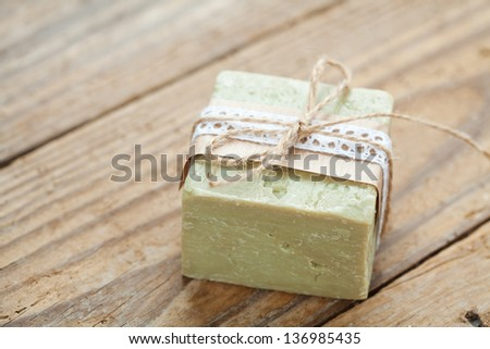 Hand made soap with decorative elements on wooden background