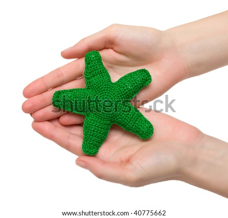 Hand made toy - green starfish in female hands. Isolation. - stock photo