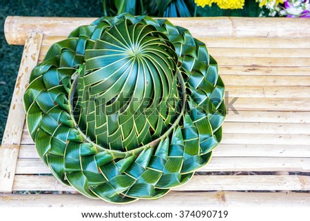 Hand made weaved hat, pleated from coconut palm leafs on a bamboo table - stock photo
