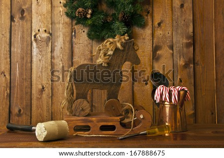 hand made wooden sled and horse with wood background and candy canes in foreground