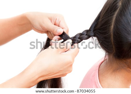 Hand making braid for little girl - stock photo
