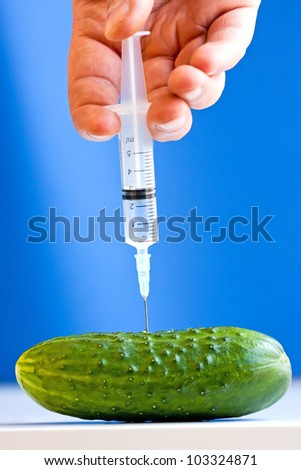 Hand making injection with syringe to cucumber on blue background. GMO concept - stock photo